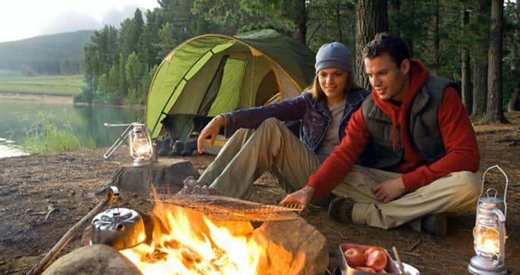 couple using camping chairs by campfire with tent