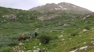 Group of boys hiking up trail with ttrekking poles