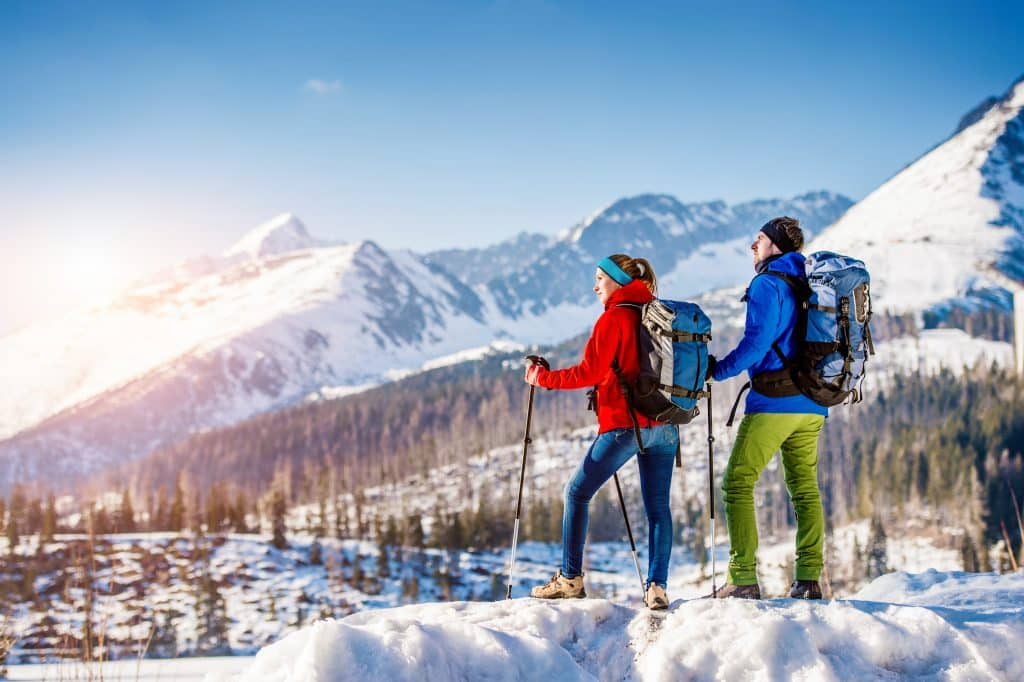Young couple using hiking sticks outside in sunny winter mountains