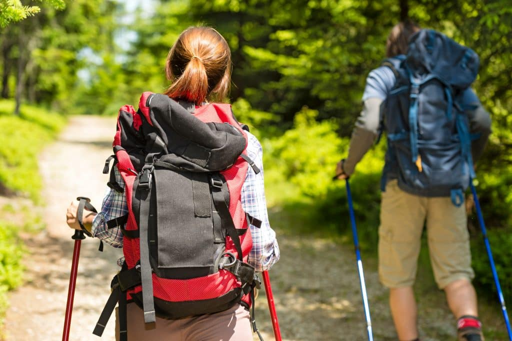 couple trekking through woods with hiking poles