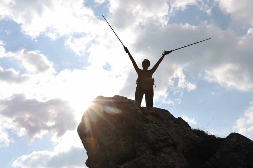 Silhouette of woman on mountaintop with trekking poles