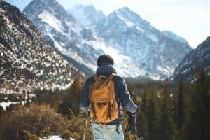 Hiker with trekking poles and backpack in snowy mountains